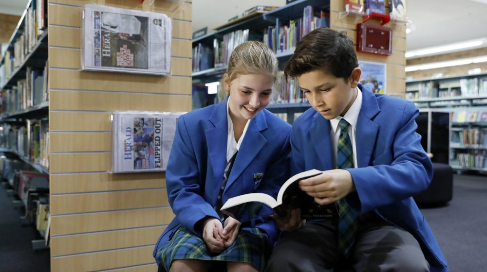 Two students reading in library