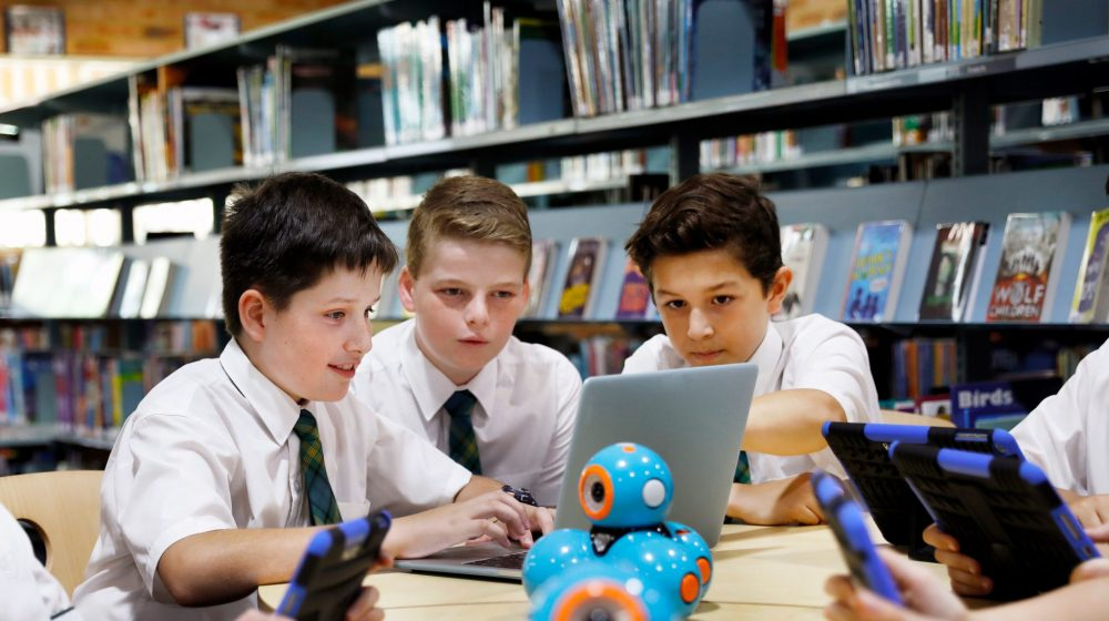 group of students looking at laptop and robots
