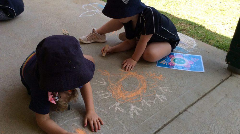 Children creating chalk art