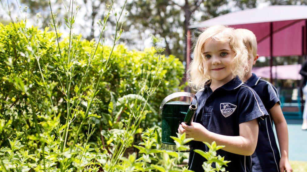 Preschool student watering plants