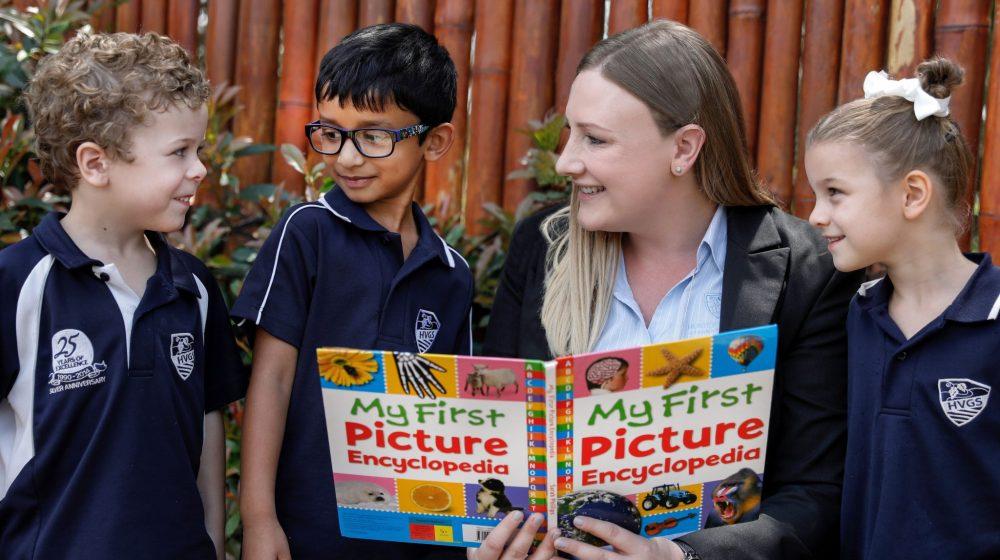 Preschool teacher reading with students