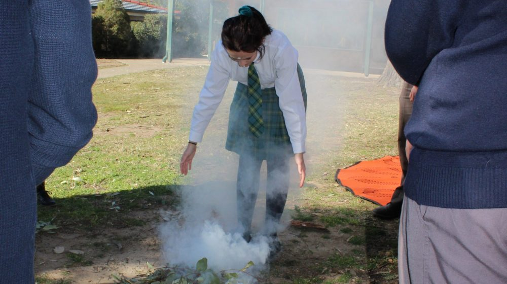 Student participating in smoking ceremony for NAIDOC week.
