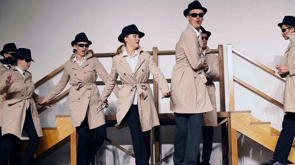 Students in trenchcoast performing the play Get Smart