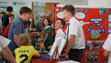 Students talking to adults about their stall