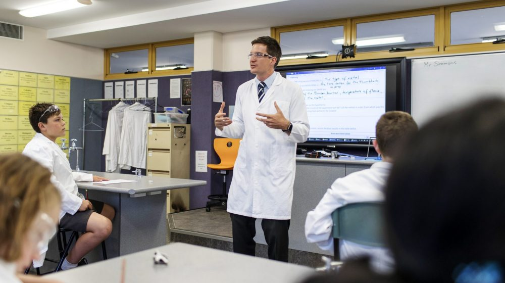 Science teacher in lab coat teaching science