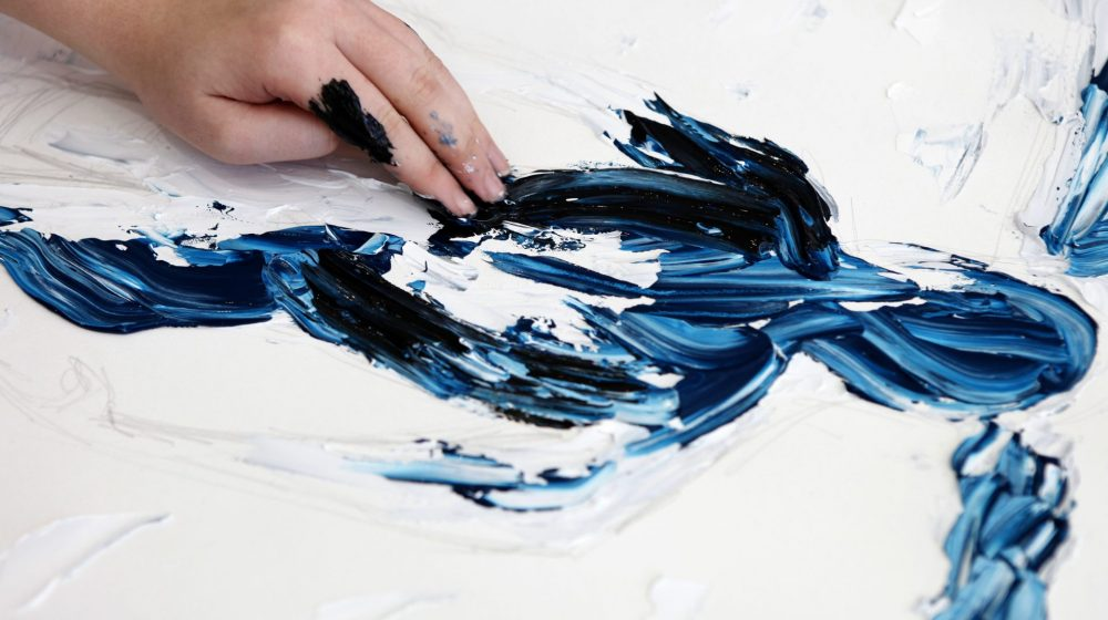 student smearing paint on canvas