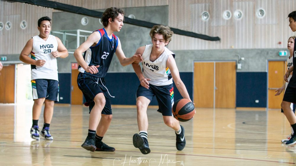 Student playing basketball in a gymnasium