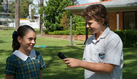 Student using a microphone to record another student