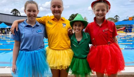 4 girls standing together wearing colourful tutus