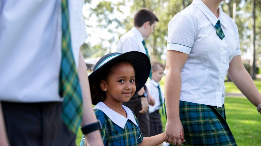 kindy student walking with older students