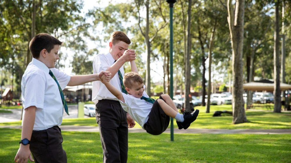 child swinging with older children