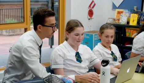 teacher assisting students