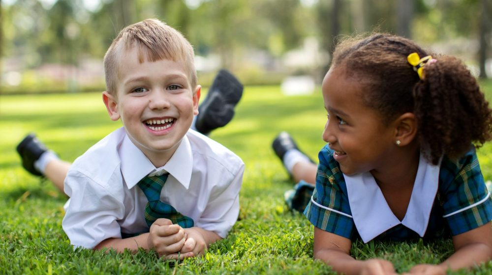 two kindergarten students hanging out on grass