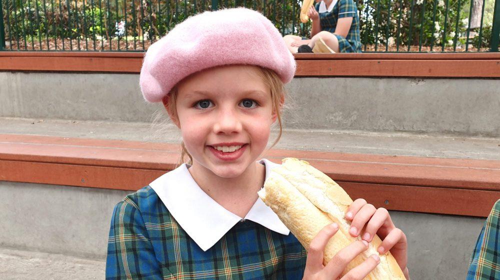 girl wearing beret eating banguette