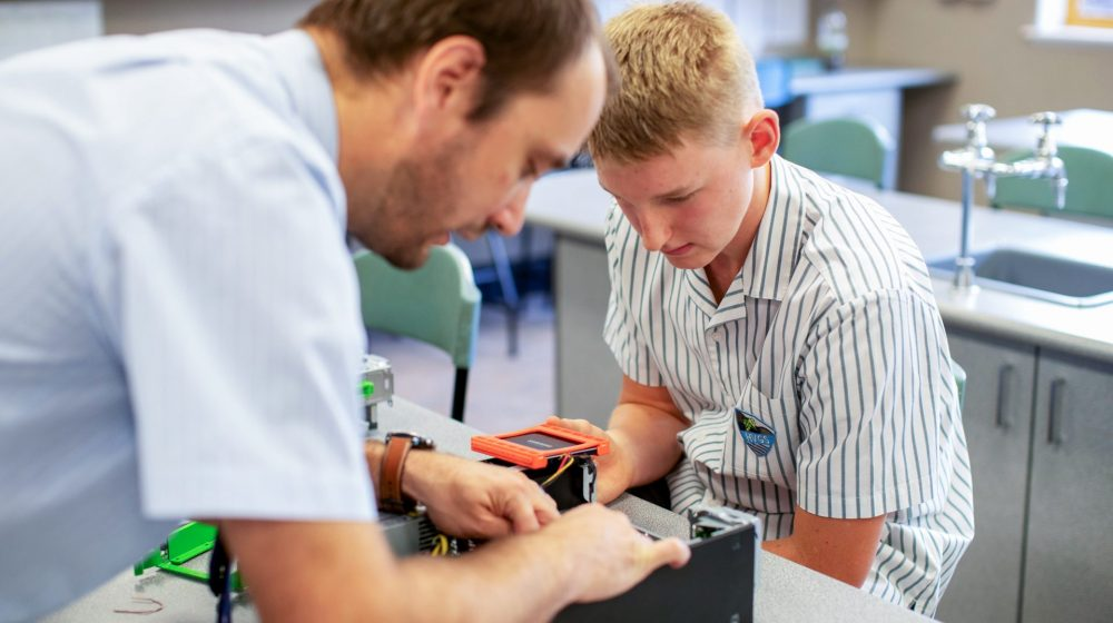student and teacher working on a computer