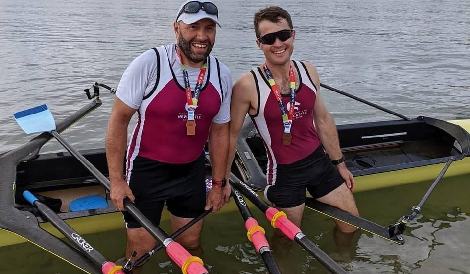 two men standing in the water near a rowing boat